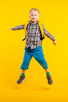 Boy jumping on yellow wall