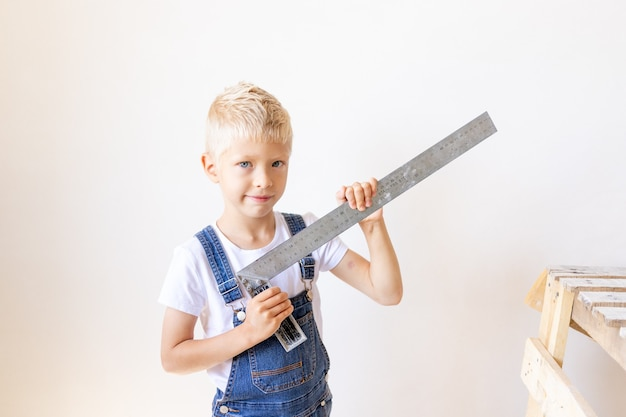 Boy in jumpsuit holding a construction ruler