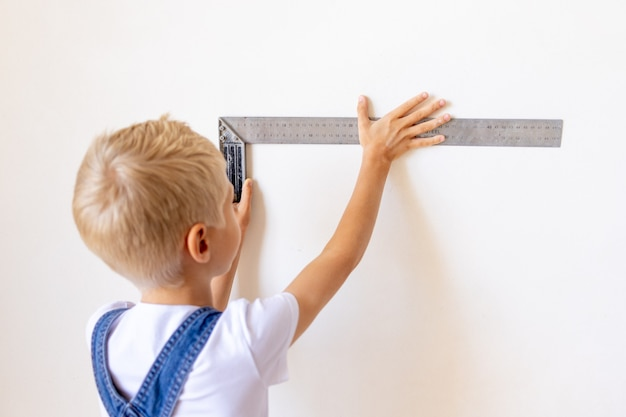 Boy in jumpsuit holding ruler