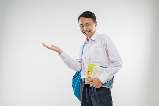 A boy in junior high school uniform offering something with a hands gesture when carrying a book and...