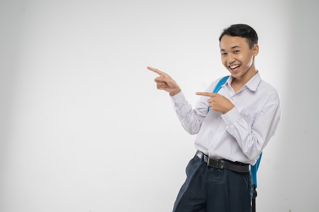 A boy in junior high school uniform smiling with finger pointing when carrying a backpack with copys...