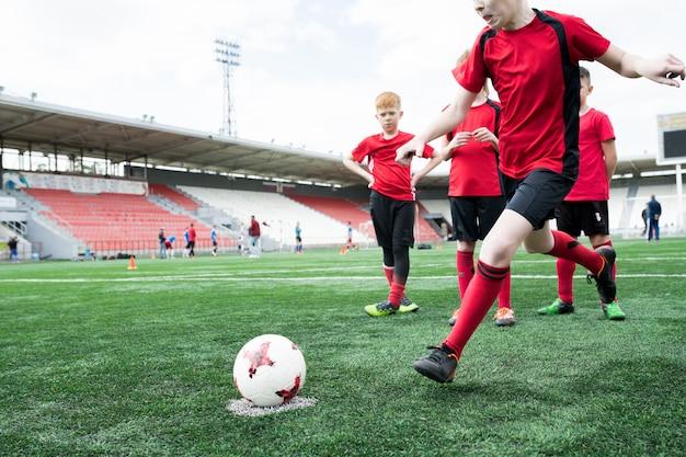 Boy kicking ball at football practice