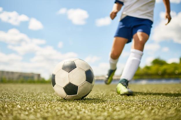 Мальчик пинает мяч в футболе
