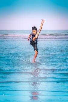 Boy kicking sea water on the beach