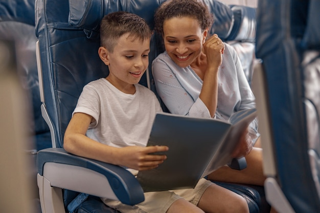 Boy, kid on board holding a book and looking trough it together with his mom during flight. cabin crew providing service to family in airplane. airline transportation and tourism concept
