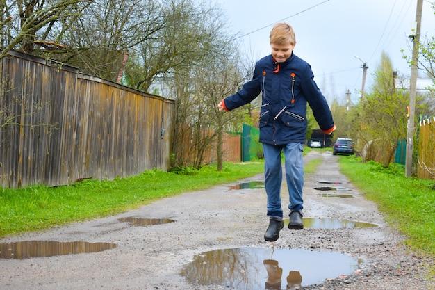 Мальчик ребенок прыгает в лужу грязи