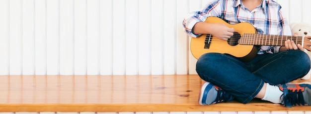 Boy kid playing guitar at home.