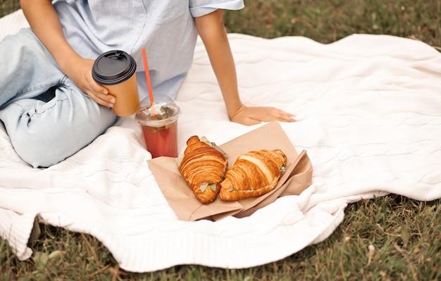焼きたてのクロワッサンとさわやかなオレンジジュースとカプチーノのグラスを手にピクニックの夏休みに座っている男の子の子供。