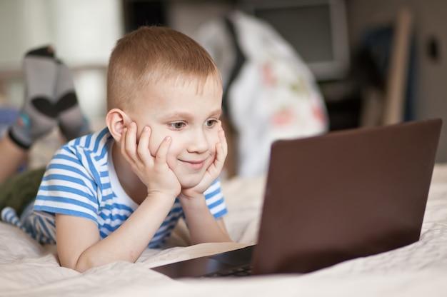 ベッドの上に座って、デジタルラップトップを使用して少年の子供