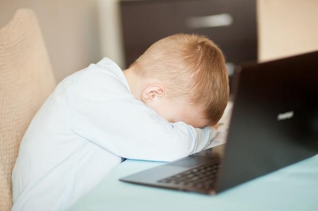 デジタルタブレットのラップトップノートブックを机の上に座っている男の子の子供。彼はとても疲れて眠りについた。子供のオンライン学習。オンライン教育の遠隔学習。