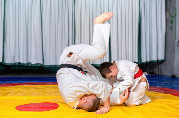 A boy in kimono is practicing martial arts with his master in the ring of a gym, boy is winning