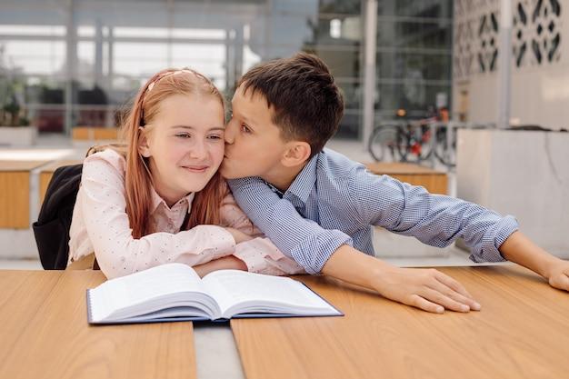 少年は校庭で少女にキスします。最初の学校の愛の概念