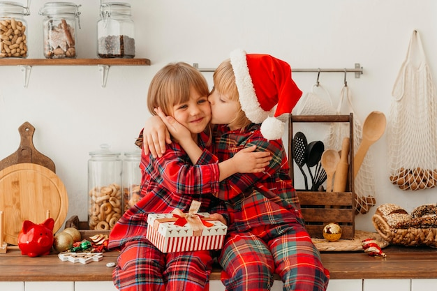 Boy kissing on the cheek his sister