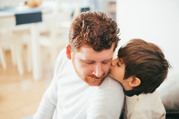Boy kissing dad on cheek