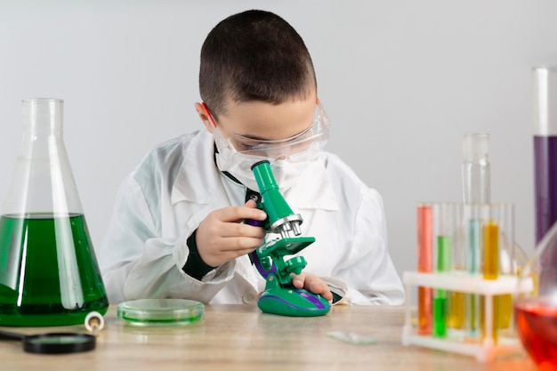 Boy in laboratory with microscope