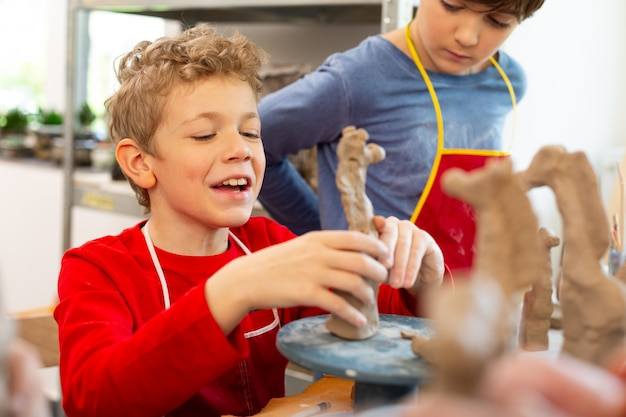 Boy laughing while modeling clay animals at art lesson