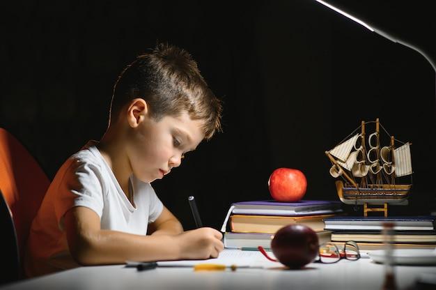 Мальчик учит уроки в домашней обстановке за столом в свете настольной лампы.