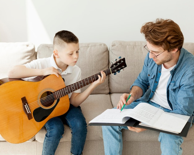 Boy learning guitar and tutor listening