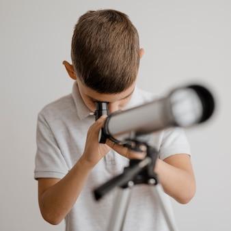 망원경 클로즈업을 사용하는 방법을 배우는 소년