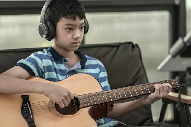 A boy learning to play the guitar, concentration on playing the music,