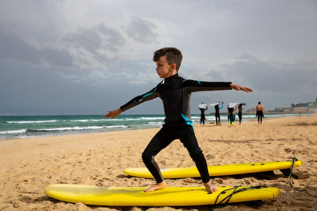 Boy learning to stand on surfboard