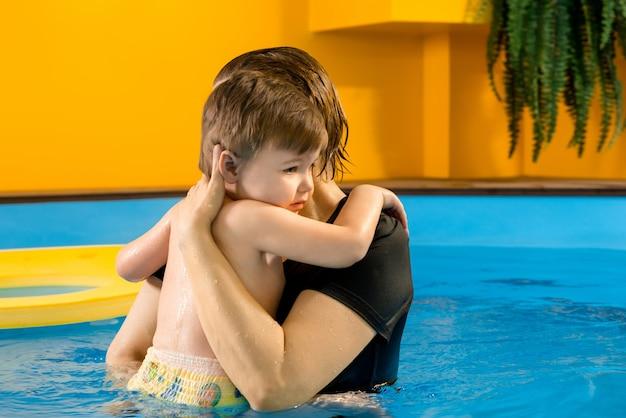 Мальчик учится плавать в бассейне с тренером
