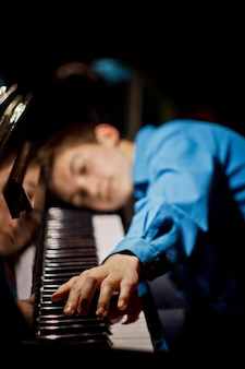 Boy lies on the keys and plays the keyboard instrument in the music school.