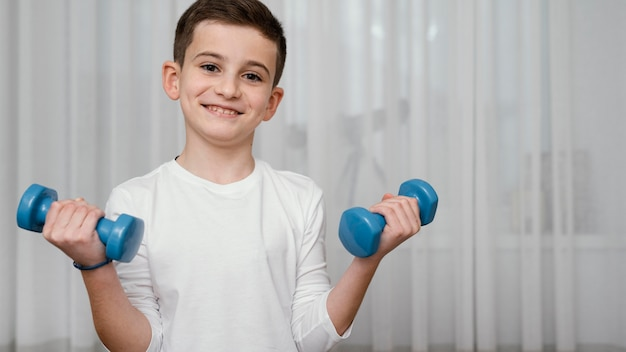 Boy lifting dumbbells workout exercises