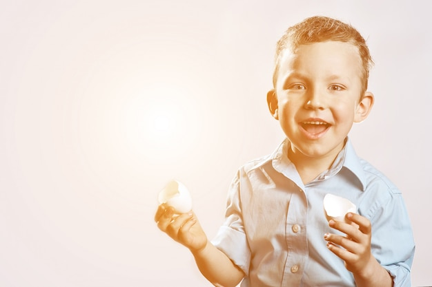 Boy in a light shirt holding a shell from the egg and smiling