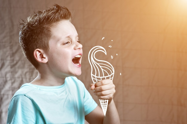 Boy in a light t-shirt eating painted ice cream from which flying spray