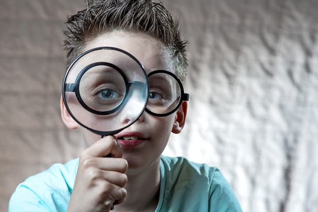 Boy in a light t-shirt and glasses looking into a large magnifying glass