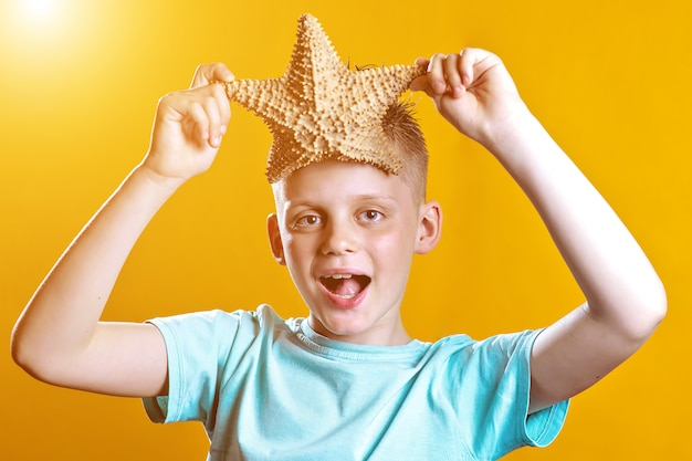 A boy in a light t-shirt holding a starfish on a yellow