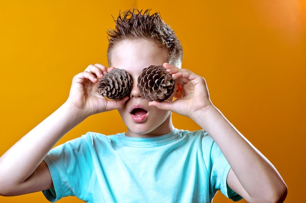 A boy in a light t-shirt put two cones to his eyes on a colored