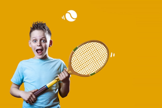 A boy in a light t-shirt with a tennis racket and a ball on orange