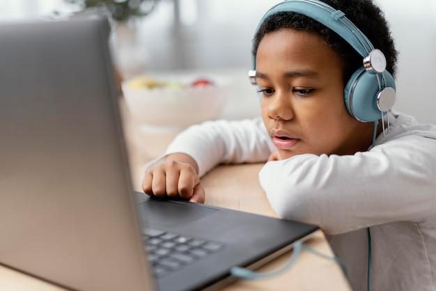 소년은 음악을 듣고 노트북을 사용