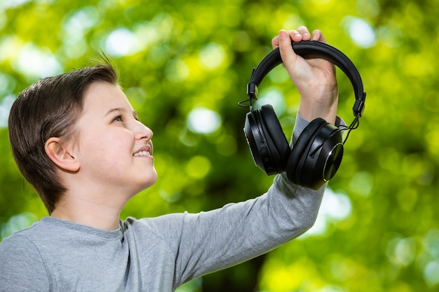 Boy  listening a music by huge headphones in outside forest