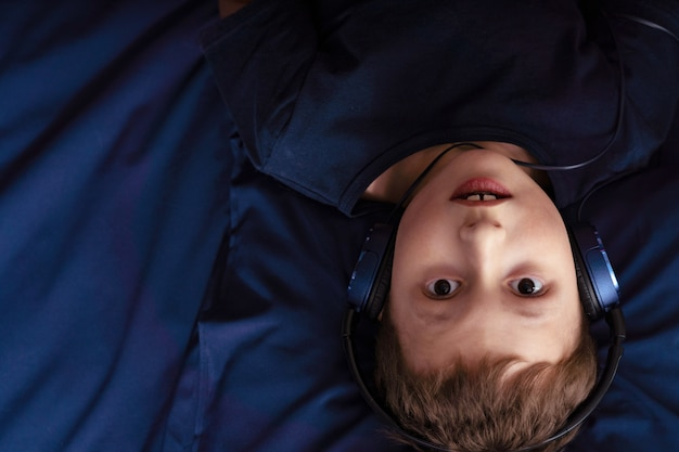Boy listening to music in headphones lying in bed