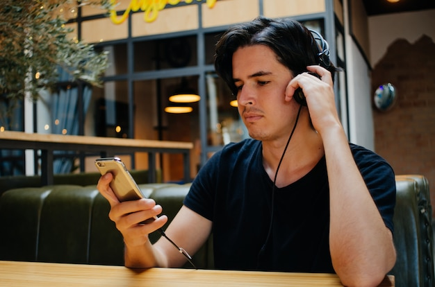 Boy listening music with headphones in a coffee shop