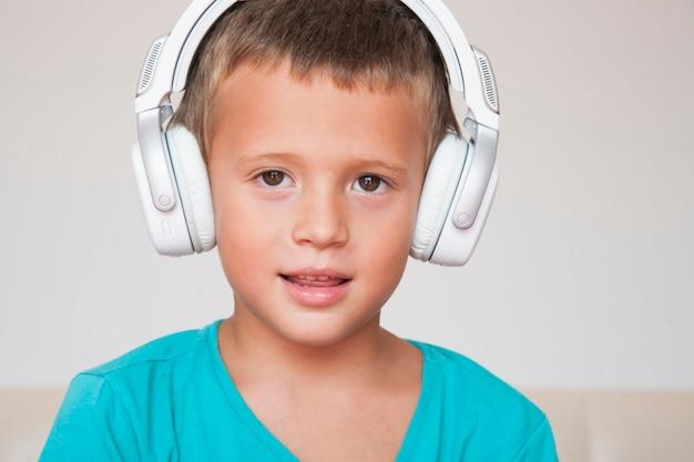イヤホンで音楽を聴いている少年。ワイヤレスヘッドホンの子供は音楽を楽しんでいます。