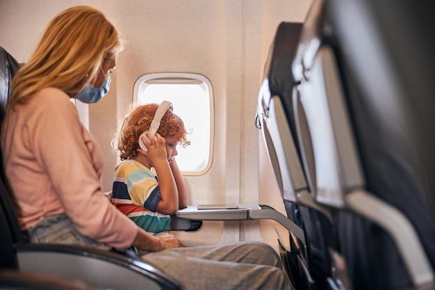 Мальчик слушает музыку через наушники на борту
