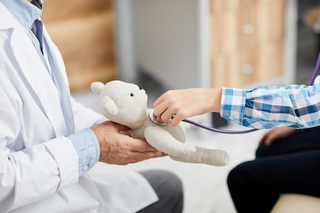 医師のオフィスでおもちゃのハートビートを聞いている少年