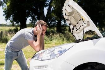Boy looking at broken down car