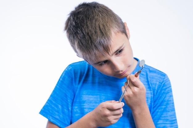 歯の鏡とスケーラーを見ている少年