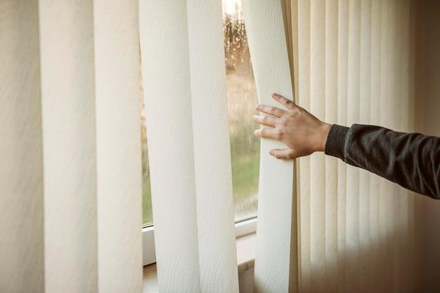 外で何が起こっているのかを見ている少年