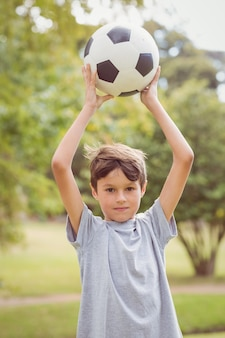 Boy looking at camera and holding a soccer ball in the park