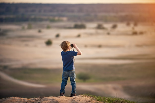 Boy looking through binoculars outdoors at sunny day