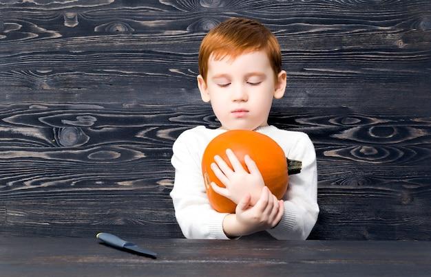 少年は熟したオレンジ色のカボチャを見ます