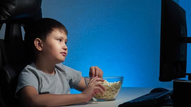 少年はコンピューターの面白いビデオを見て、ポップコーンを食べる