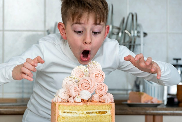 Boy looks at big beautiful cake in surprise and admiration. child wants to eat the whole cake.