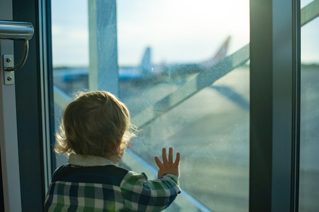 少年は空港の窓の外を見る